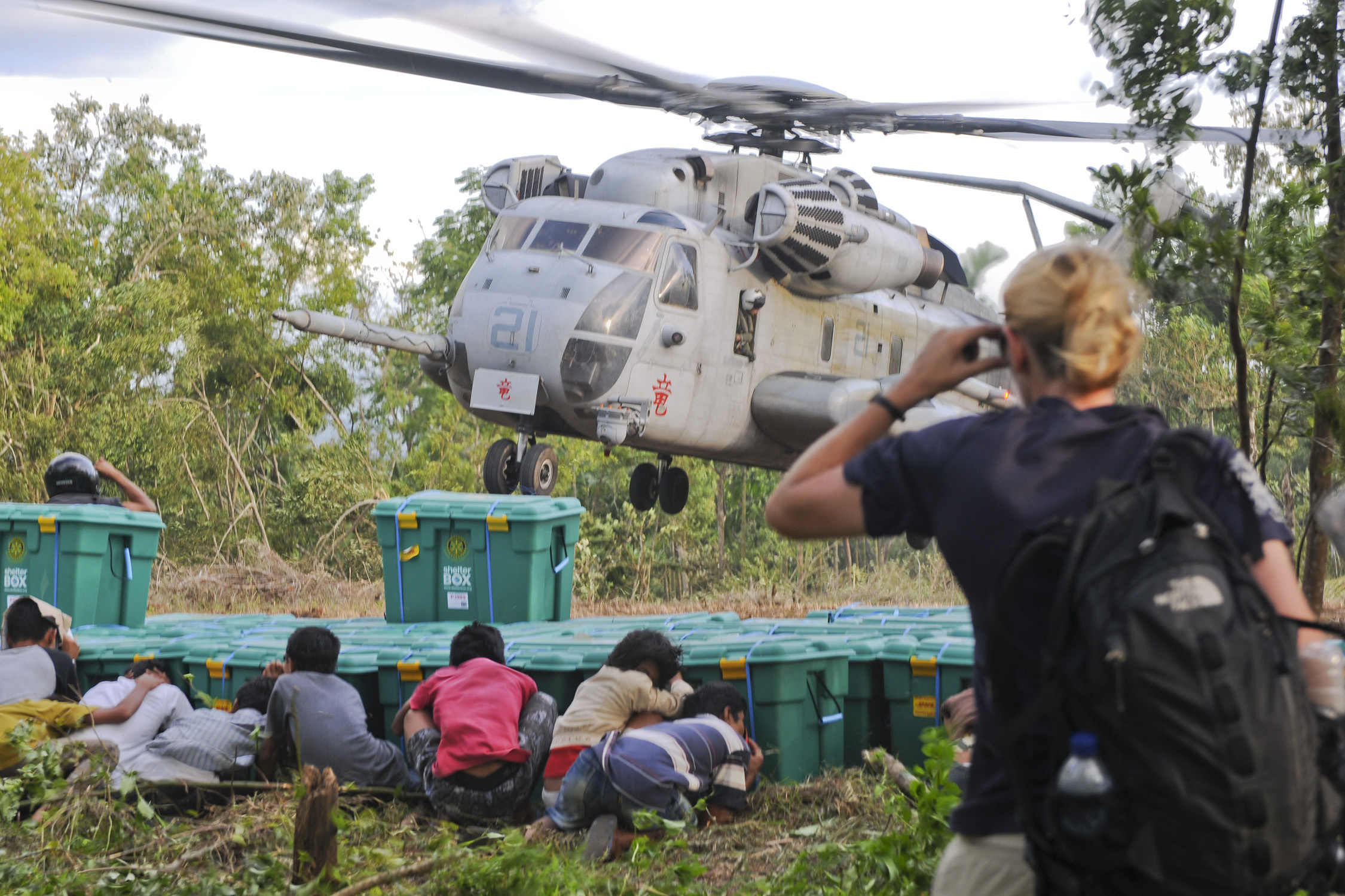 Children taking shelter behind a stack of Shelter boxes as a helicopter lands