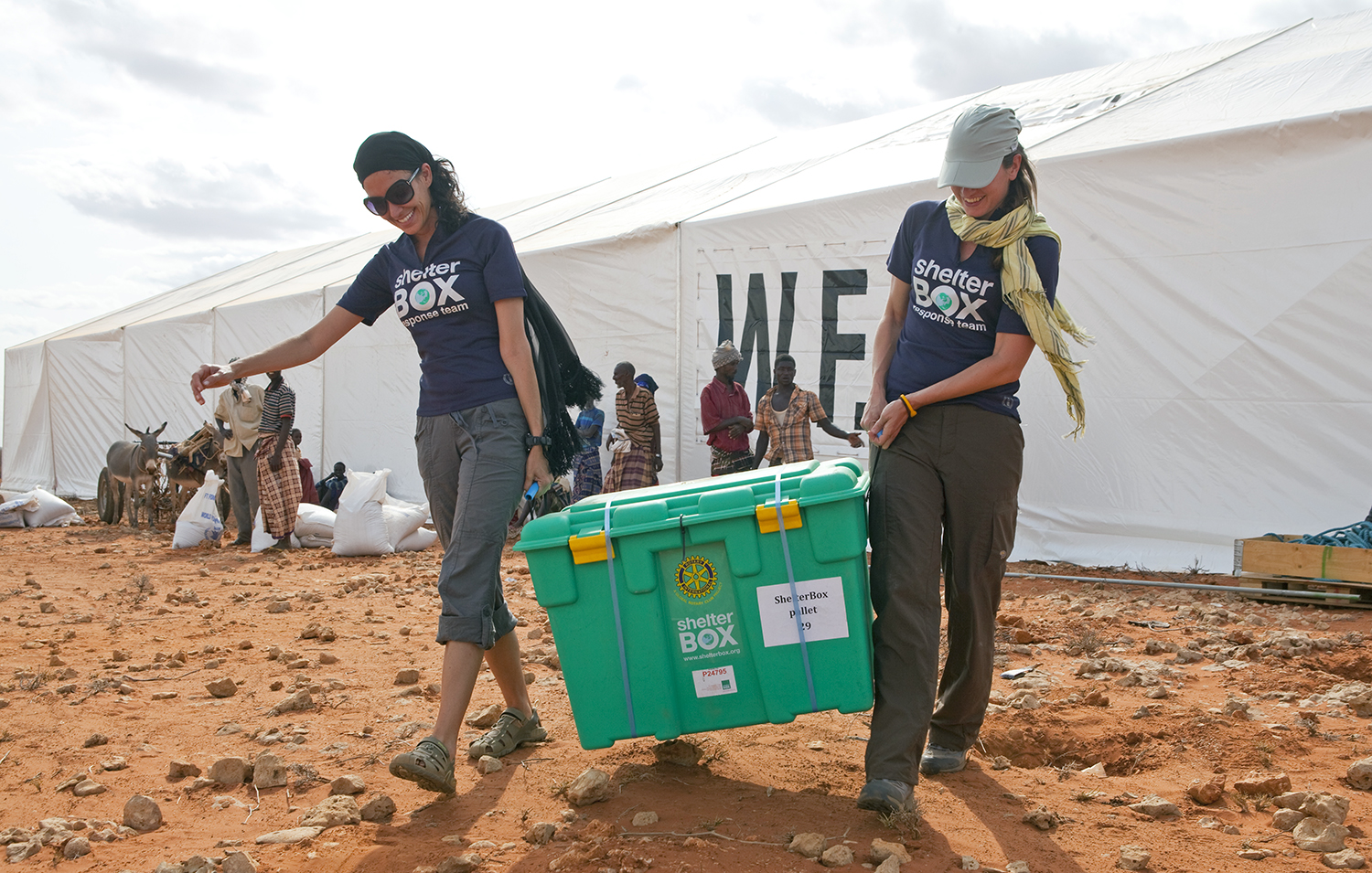 L-R Emily LoSavio (USA) and Rebecca Ridgeway (UK) carry the first of 1600 destined for Dolo Ado at the Haloweyn Refugee Camp, Somali Region, Ethiopia