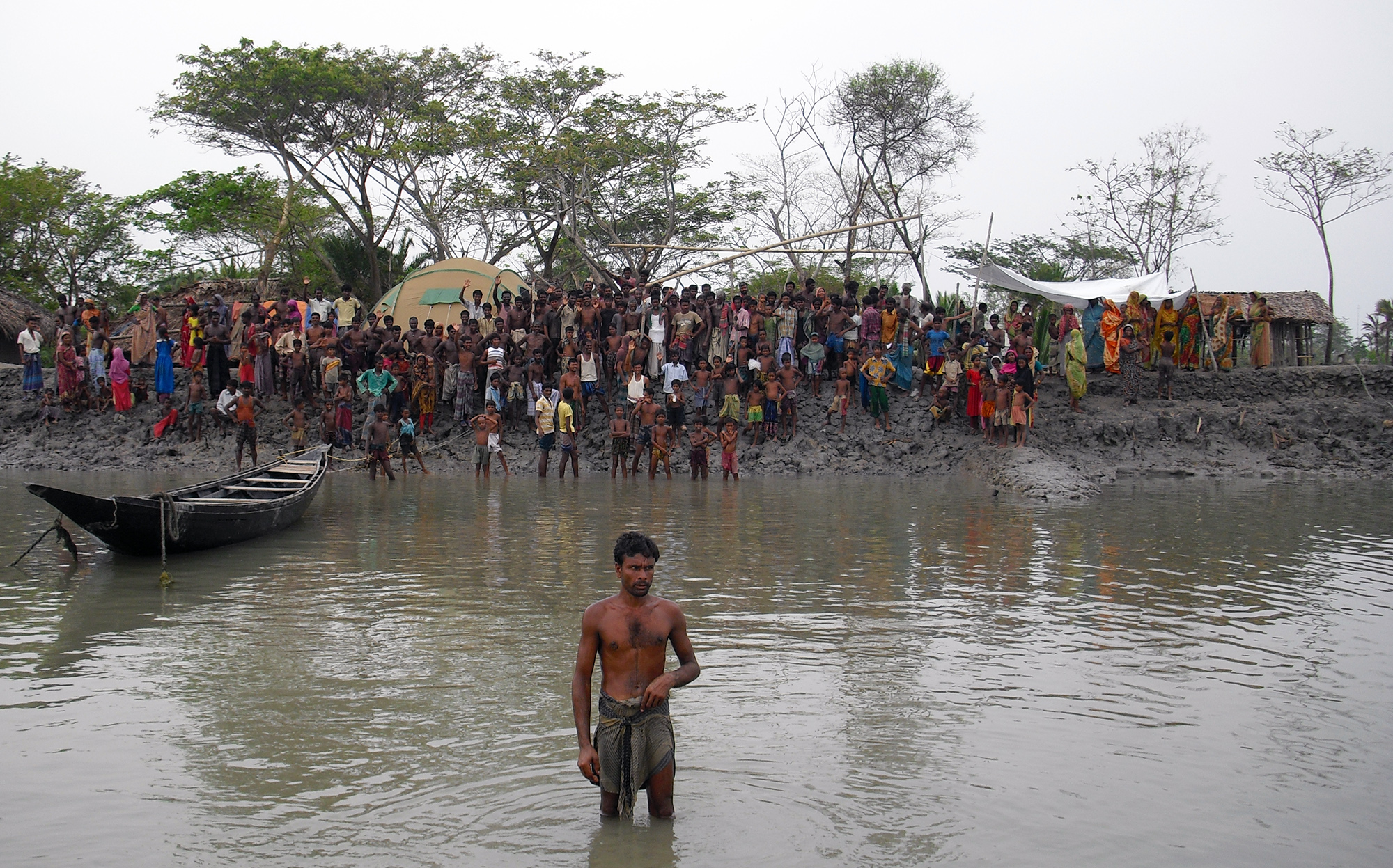 People waiting for aid at the riverbank