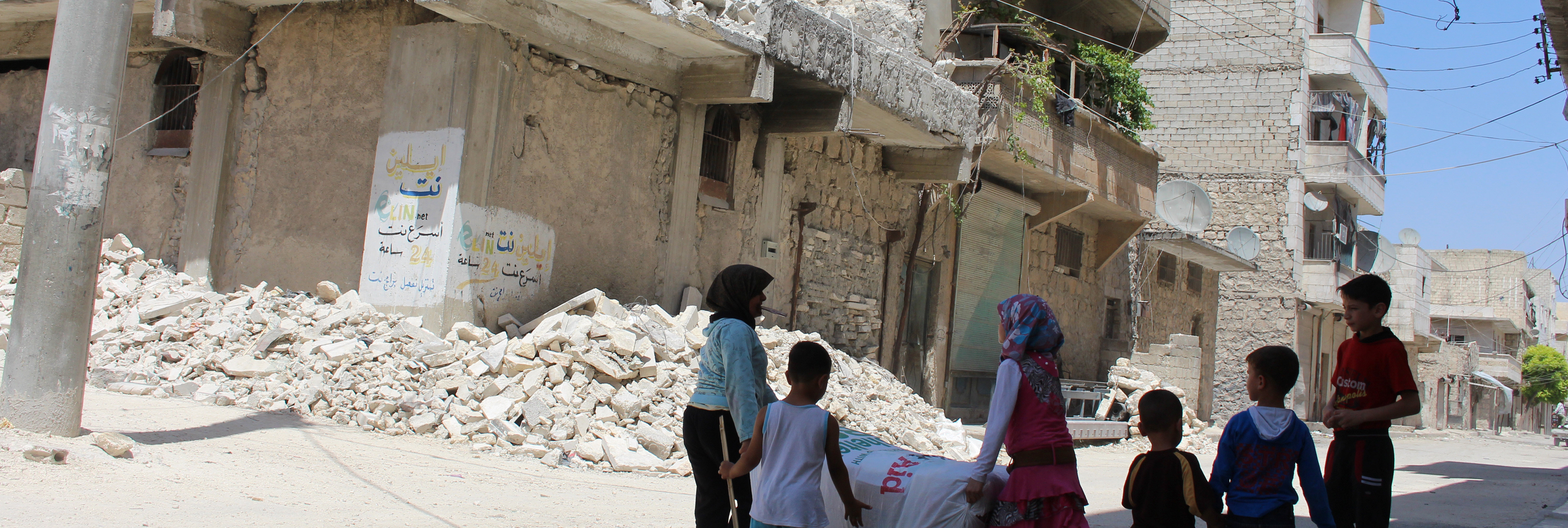 Kids play in street next to buildings damaged by bombing, Syria.