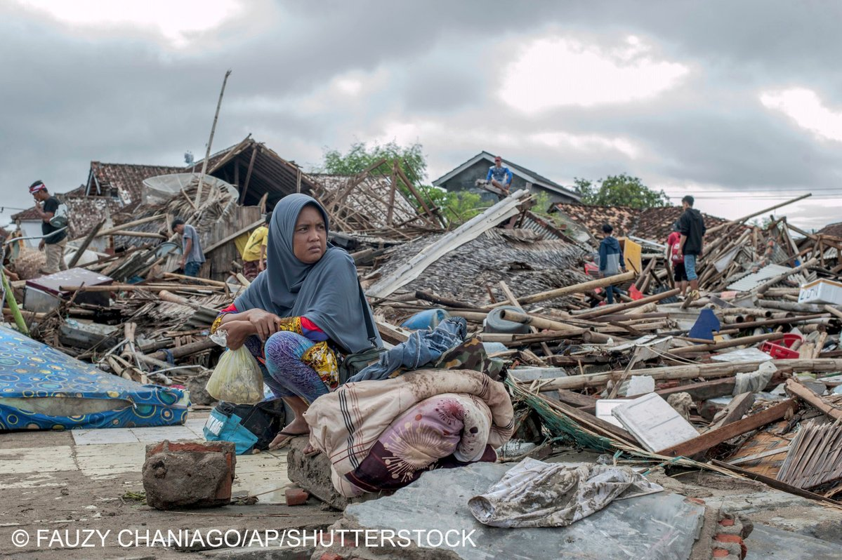 A tsunami survivor sits on a pice of debris as she salvages items from the location of her house in Sumur, Indonesia, . Doctors worked to save injured victims while hundreds of military and volunteers scoured debris-strewn beaches in search of survivors Monday after a deadly tsunami gushed ashore without warning on Indonesian islands on a busy holiday weekend.