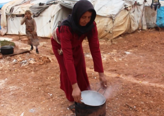 Ayman preparing to cook with boiling water outside