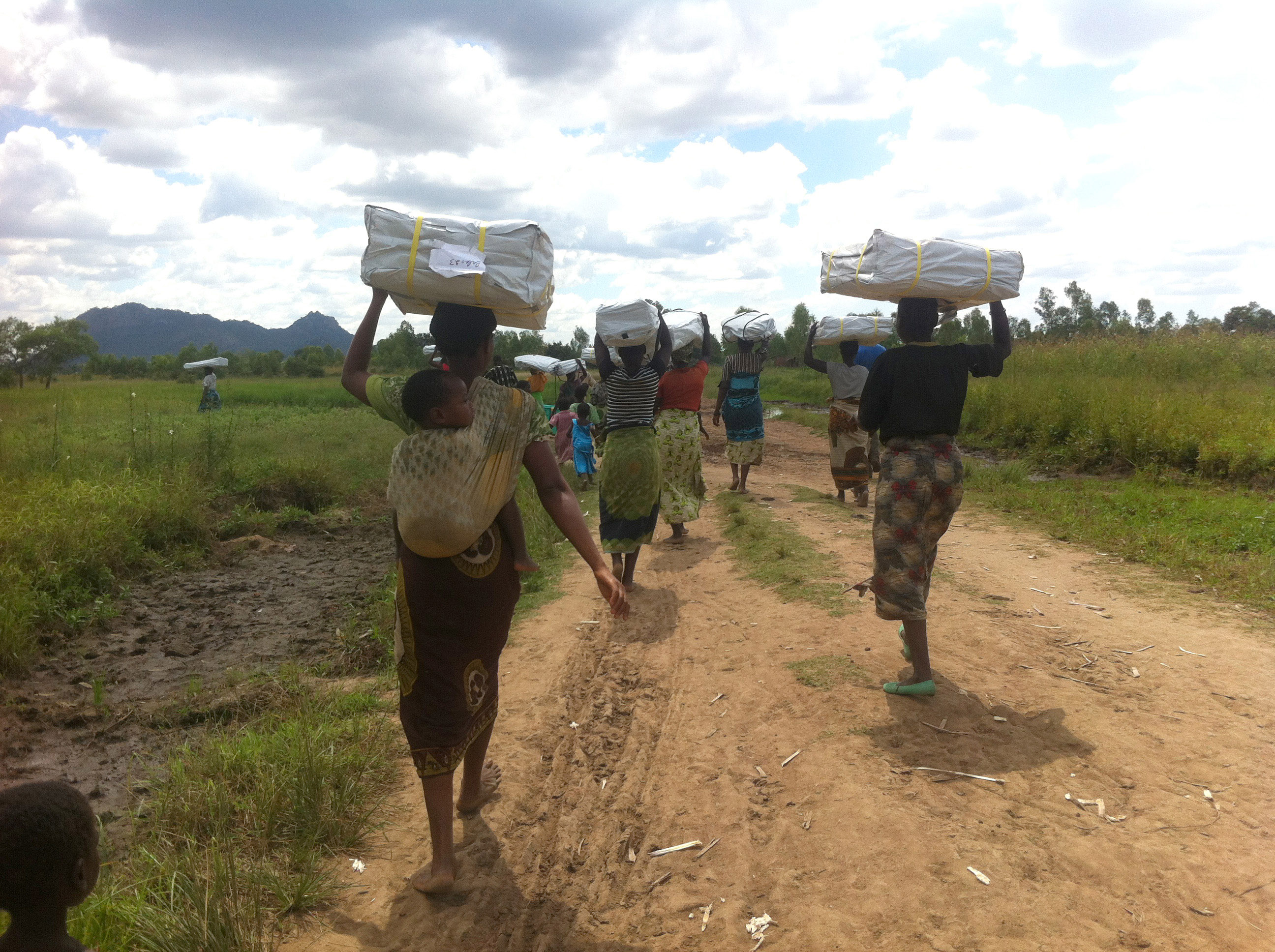 Women holding tarpaulins after flooding, Malawi