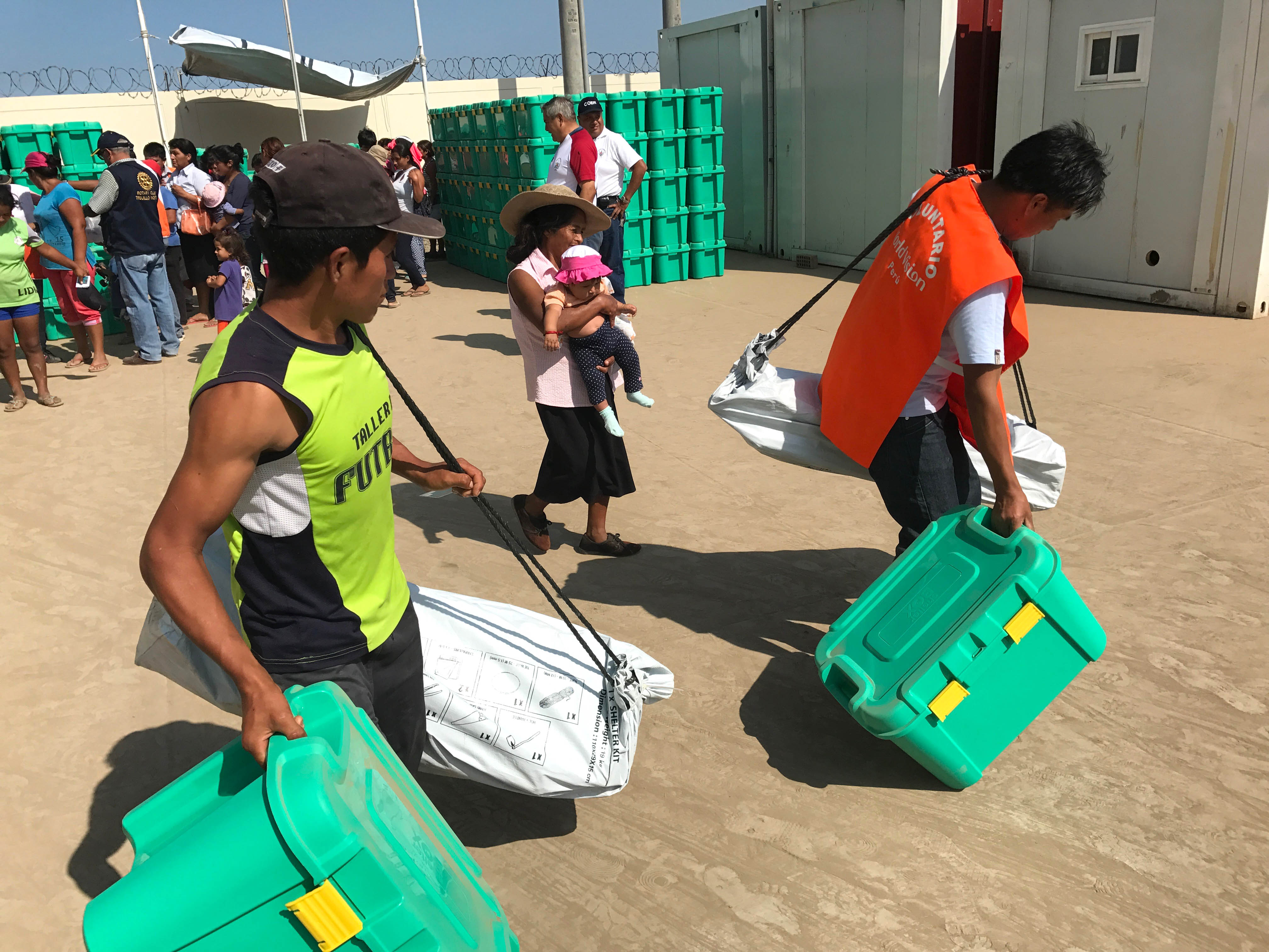Young men carrying a full ShelterBox and ShelterKit each