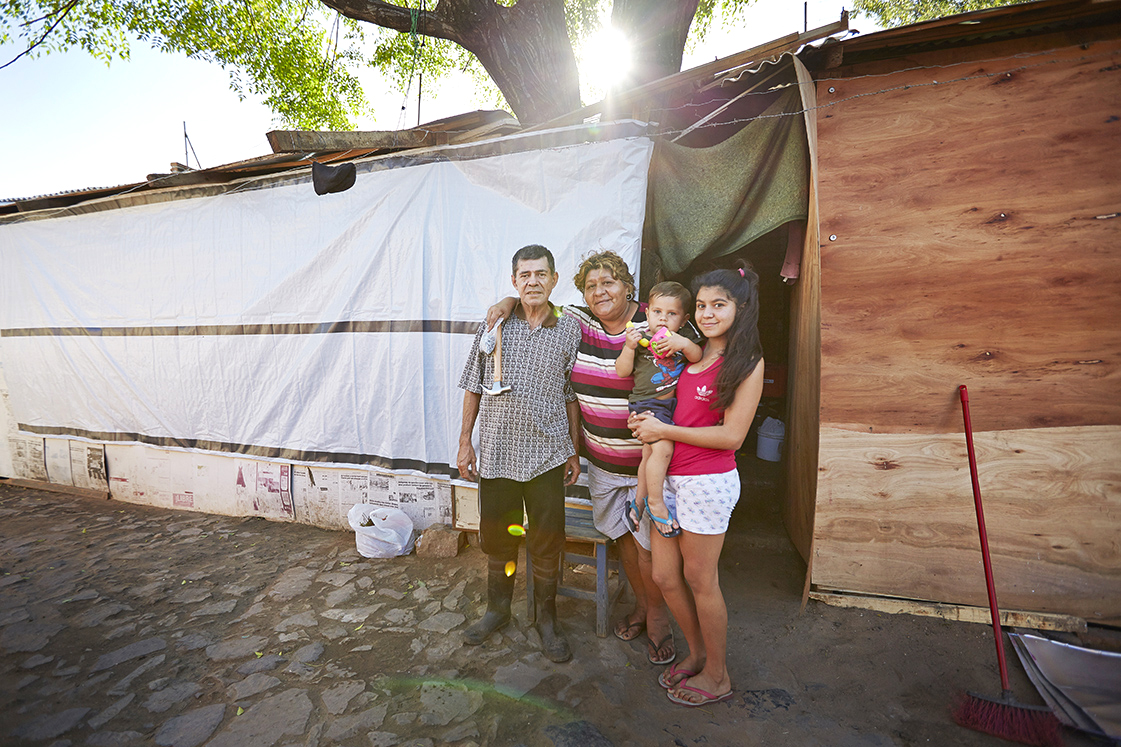Family standing outside their repaired home