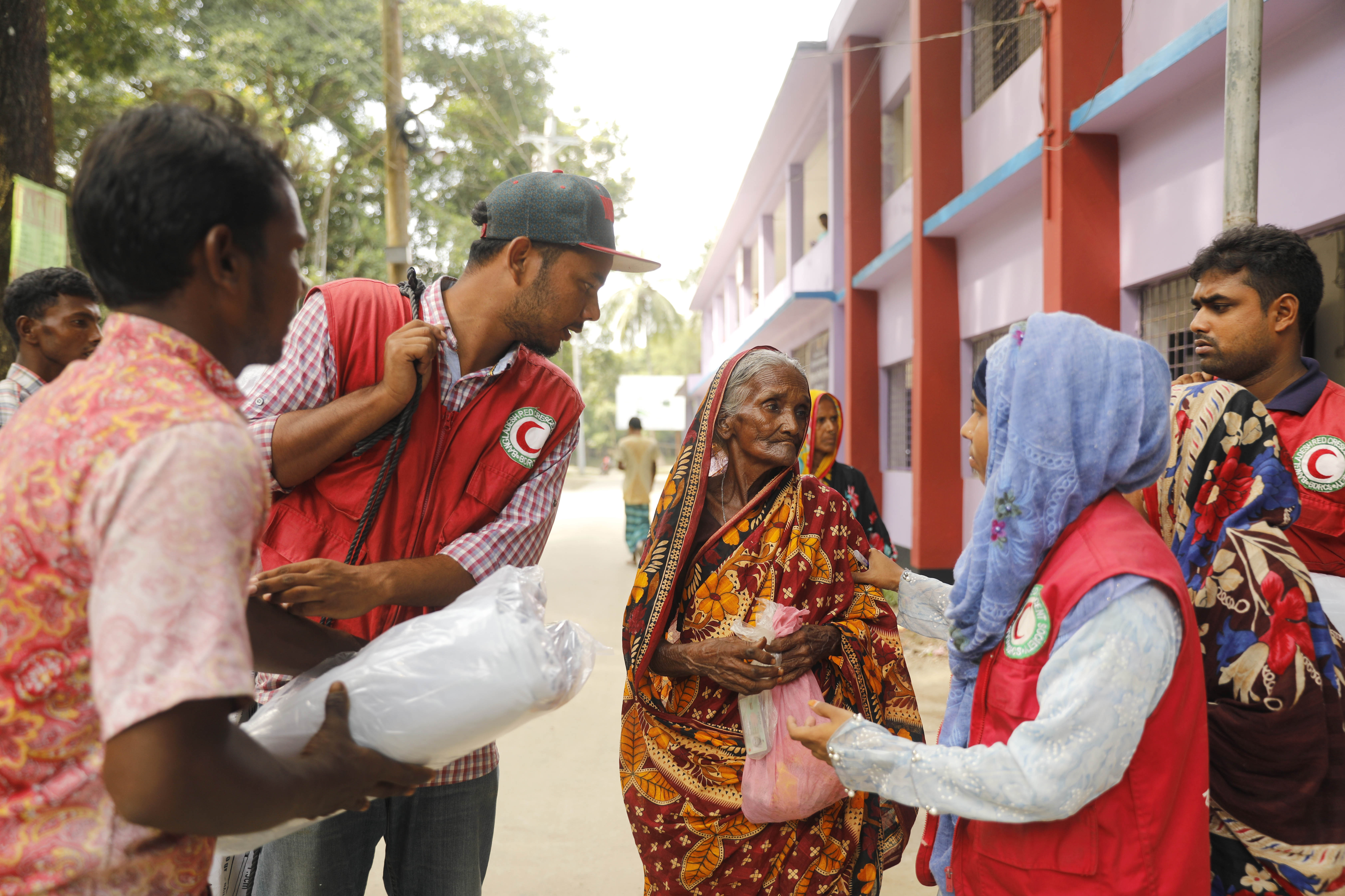 Members of the Bangladesh Red Crescent society help an elderly woman