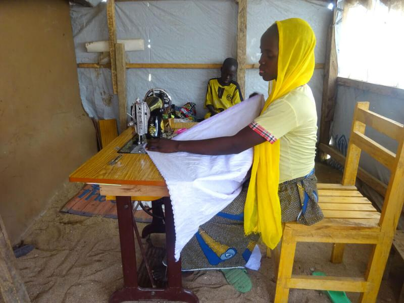 Esther working in a home reinforced with the ShelterBox tarpaulin