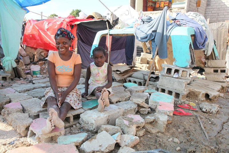 Mother and daughter sit among rubble, Haiti 2010.