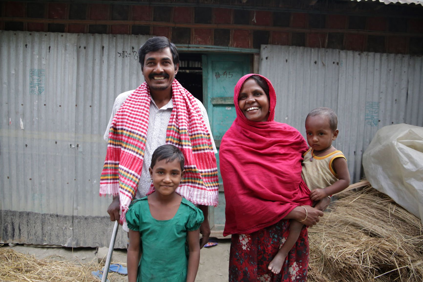 Behula, her husband, and 2 of their children outside their repaired home