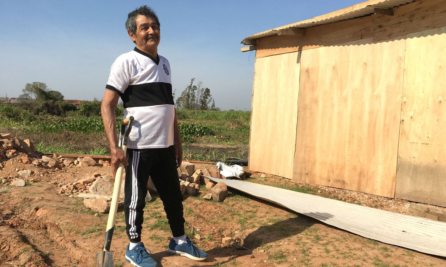 Cecilio poses alongside his newly built home