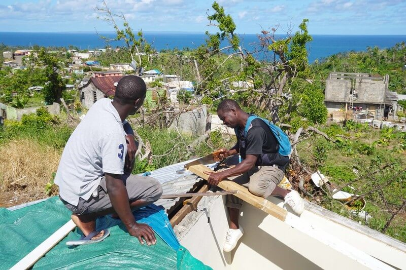 Team members rebuild Simon's roof with the ocean in back