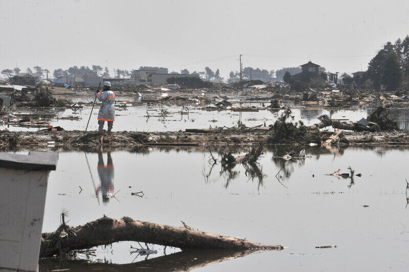 Aid worker gazing across the waterlogged landscape