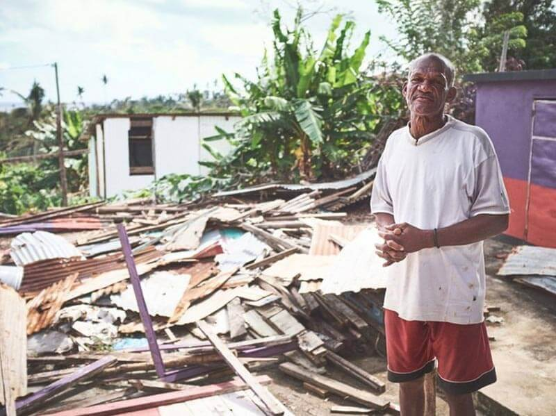 Man standing next to what used to be his home