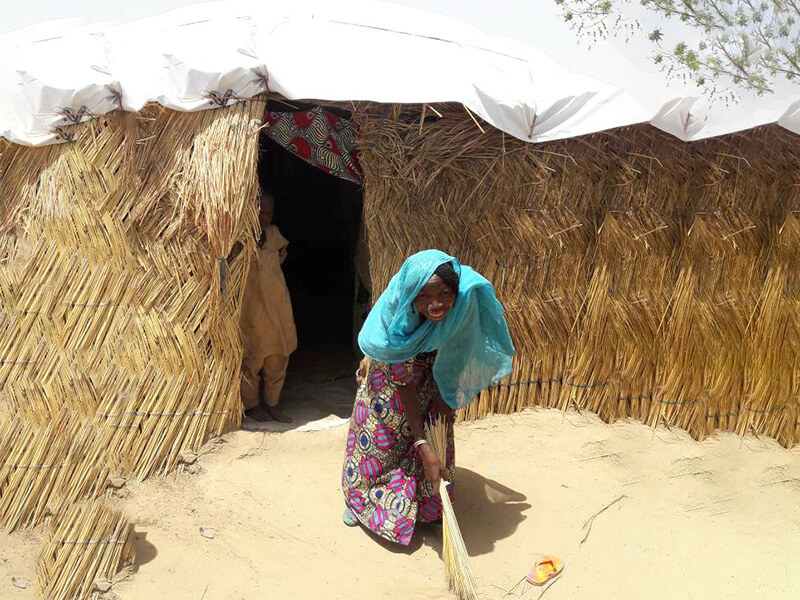 Falmata enjoying herself outside a structure with a roof using the ShelterBox tarpaulin