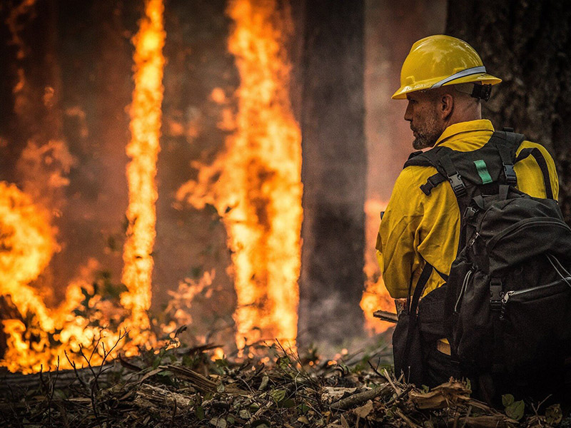A firefighter faces the flames