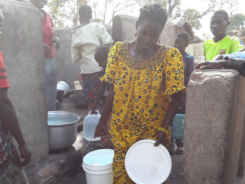 Rosalie and others gathering water, an essntial task that is delegated to female refugees 75% of the time