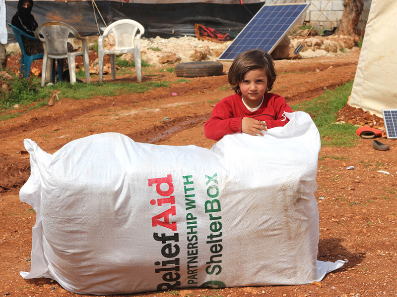 Child resting on large Relief Aid ShelterBox package, Syria 2020