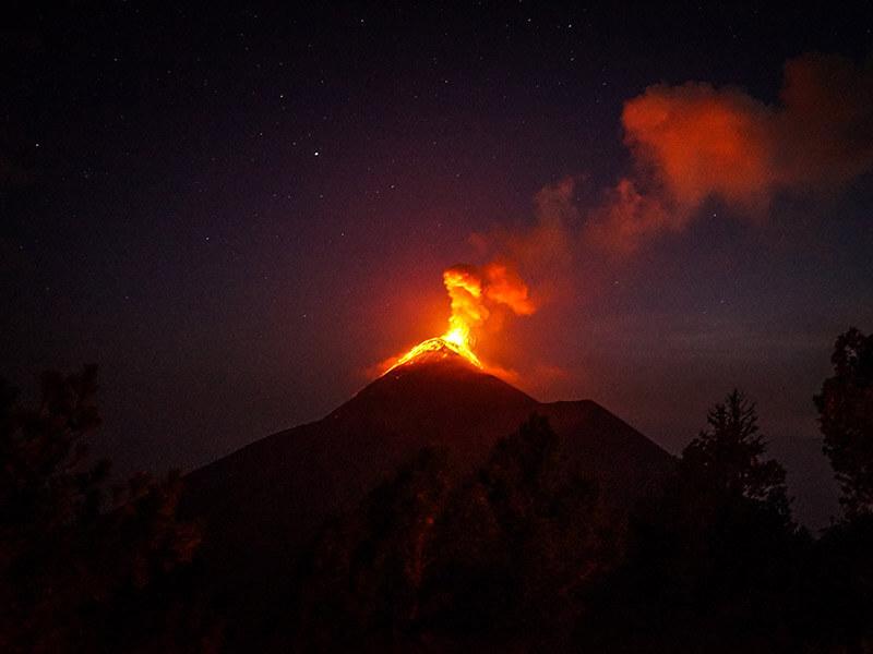 An eruption lights up the night sky orange.