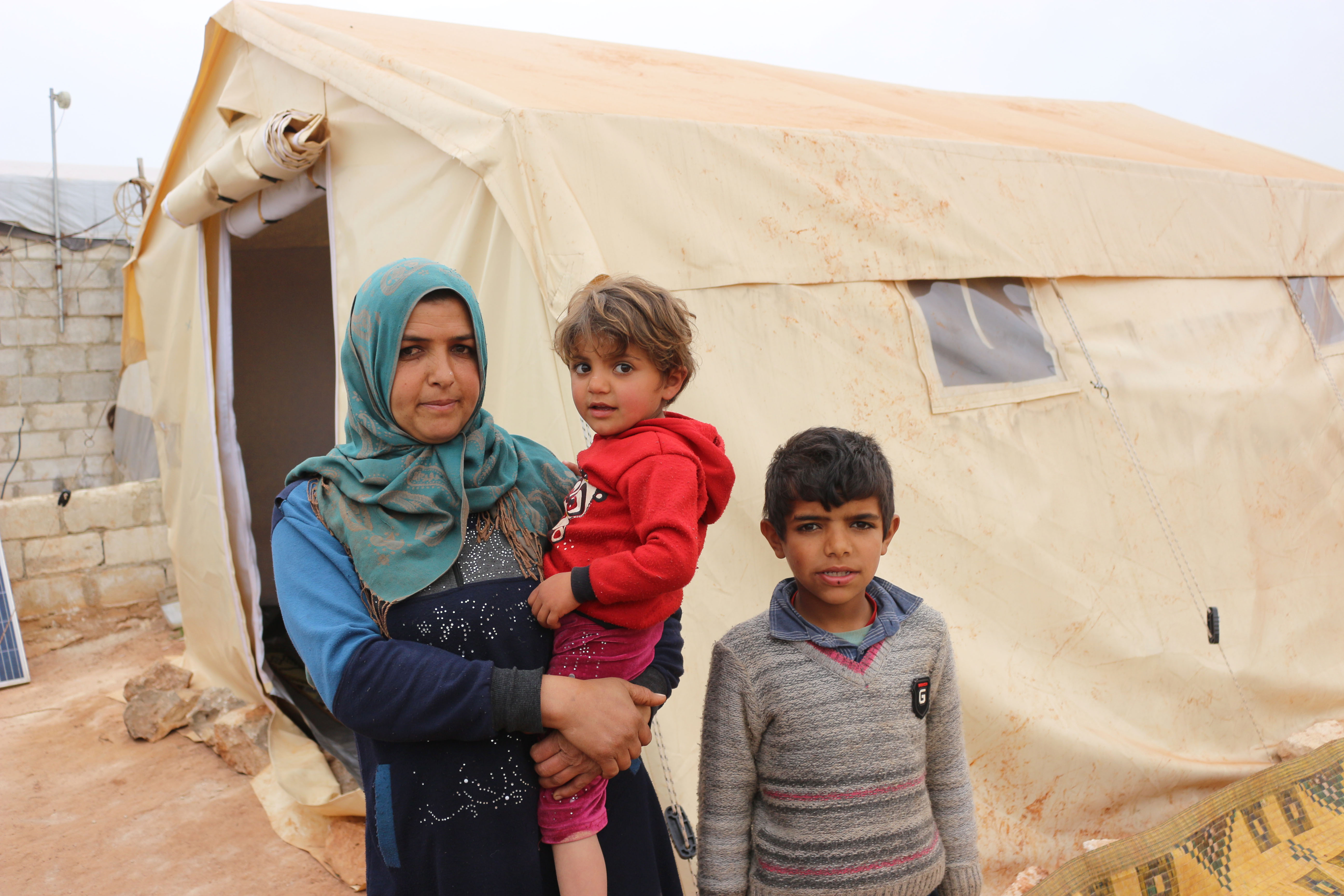 Woman and her two boys outside their tent