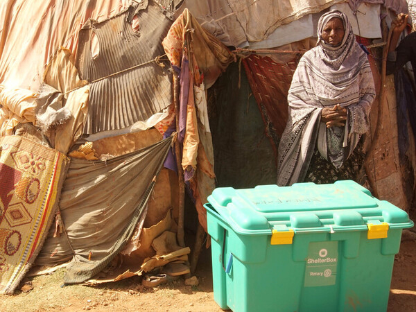 Woman with a new ShelterBox outside her home
