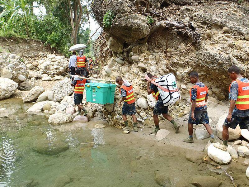 Carrying a heavy shelter box and kit over rocky terrain by a pond