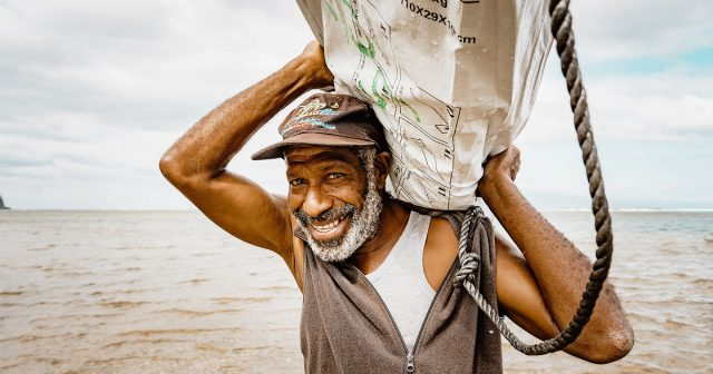 Man carrying shelter kit from a boat to land