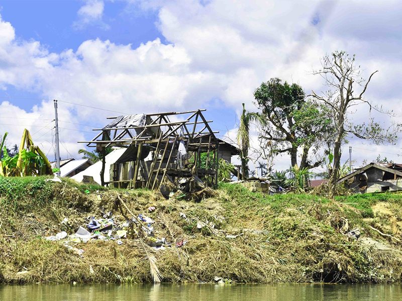 Debris scattered near a waterfront home, stripped of its roof and walls