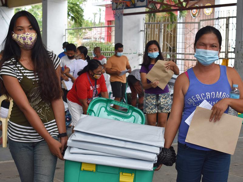 Filipino women with a ShelterBox and tarpaulin sheets