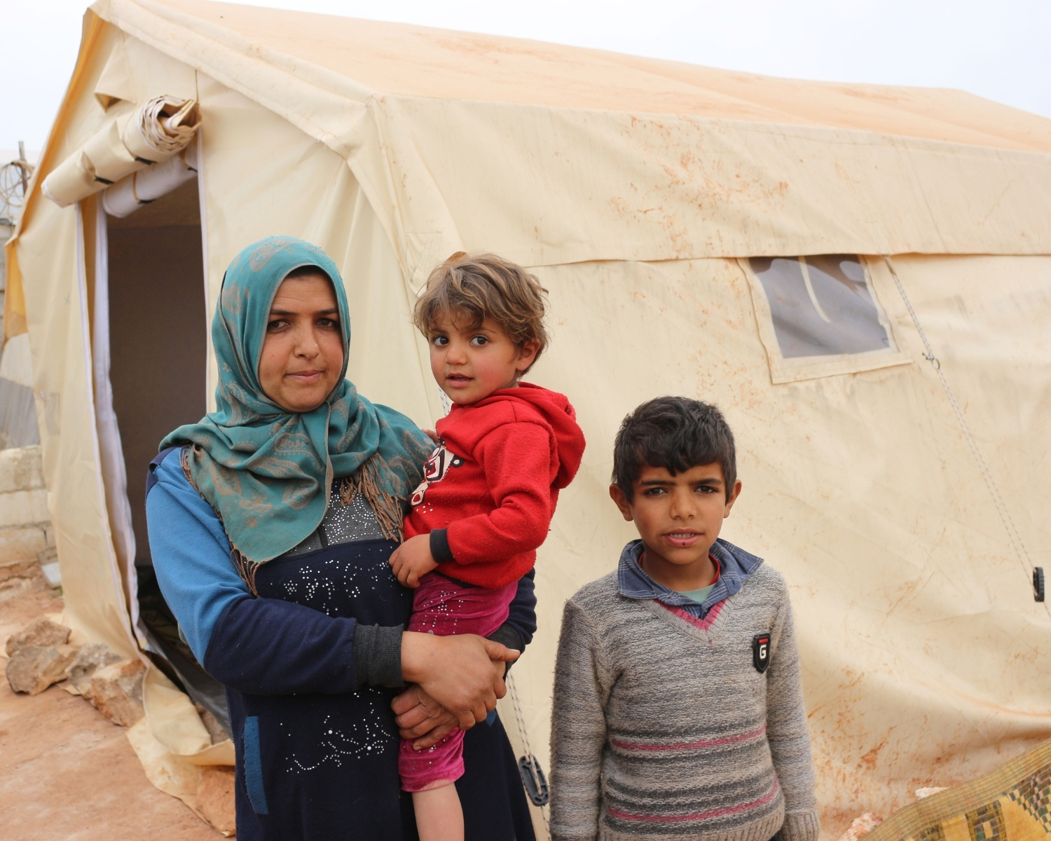 Syrian family outside tent