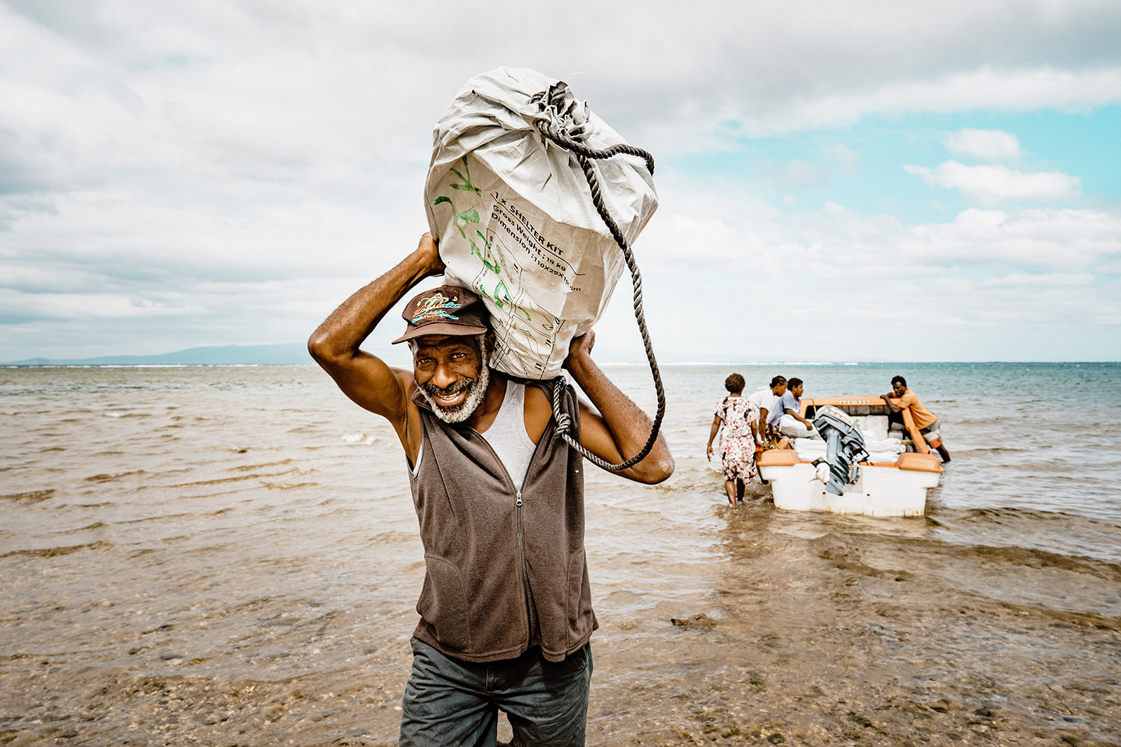 Man carries a shelter kit to land from a boat in Vanuatu