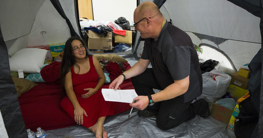 ShelterBox set up privacy tents in the American Legion Post 658 as they respond to the aftermath of Hurricane Harvey. Tamara Richards, 32 weeks pregnant, talks with ShelterBox Operations Team Lead Andrew Clark