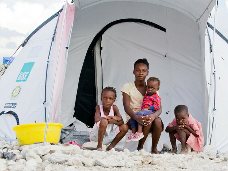 A family in Haiti sits outside of a ShelterBox tent they received