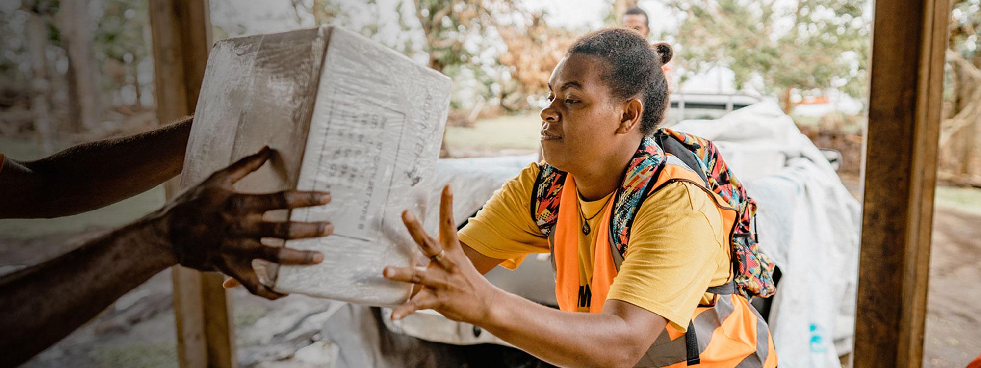 Woman passes aid box in Vanuatu