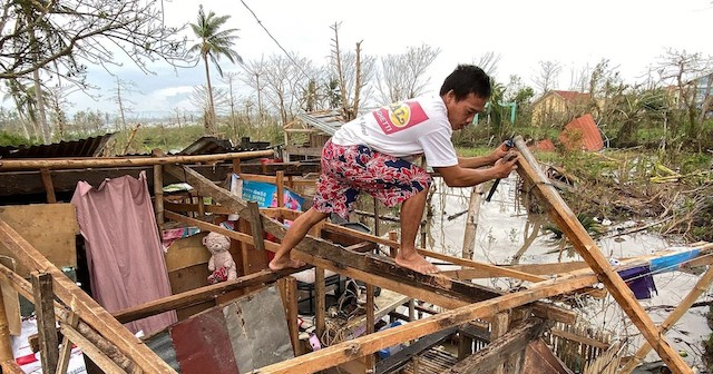 Filipino Man rebuilding after Typhoon Goni Rolly