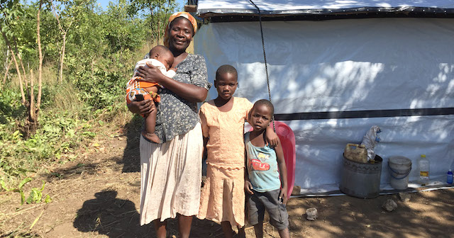 Grace and her family outside their tent