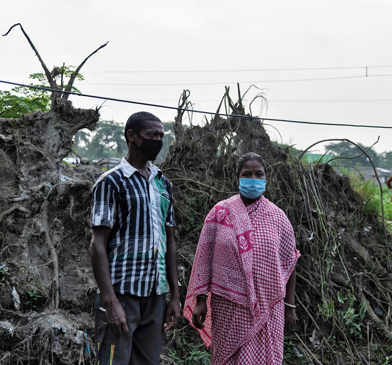 Phuleswari standing in front of mud, roots, and grass lifted up by the cyclone and flood waters